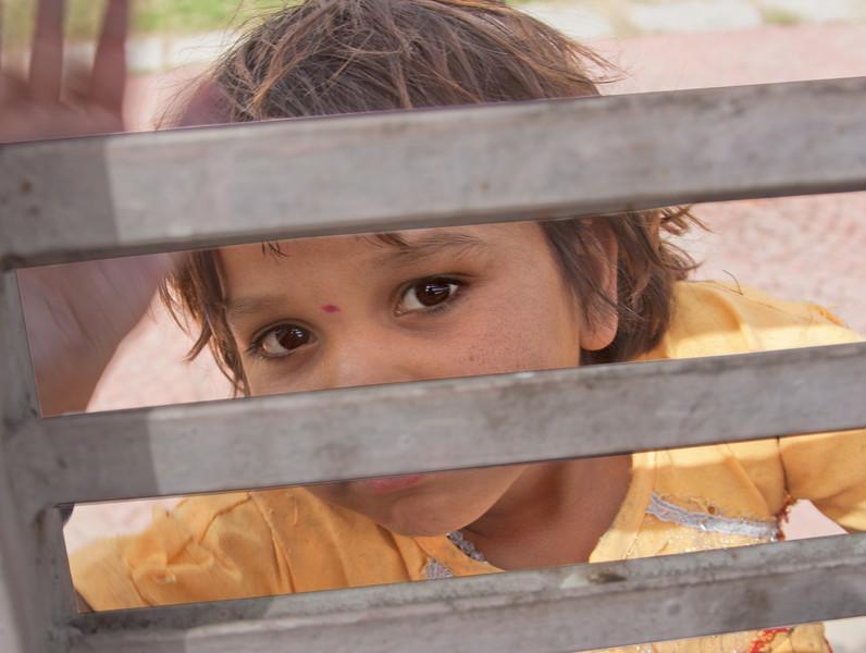 little girl looking through a gate - Delhi, India