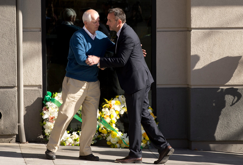 . Berkeley Mayor Tom Bates, left, embraces Philip Grant, Irish Consul General to the Western United States, after they laid two wreaths at the scene where a balcony collapsed, sending 13 people plunging to the street below, Tuesday, June 16, 2015, in Berkeley, Calif. Six people were killed, and seven more were transported to area hospitals. (D. Ross Cameron/Bay Area News Group)
