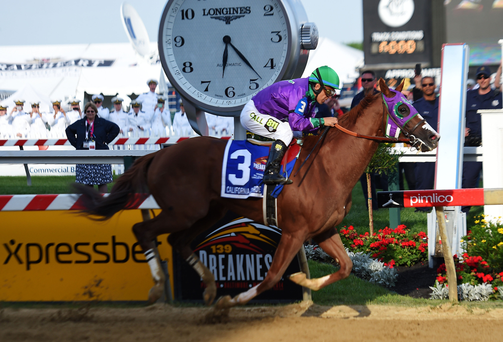 . California Chrome #3, ridden by Victor Espinoza, crosses the finishline to win the 139th running of the Preakness Stakes at Pimlico Race Course on May 17, 2014 in Baltimore, Maryland.  (Photo by Jim Dietz/Getty Images)