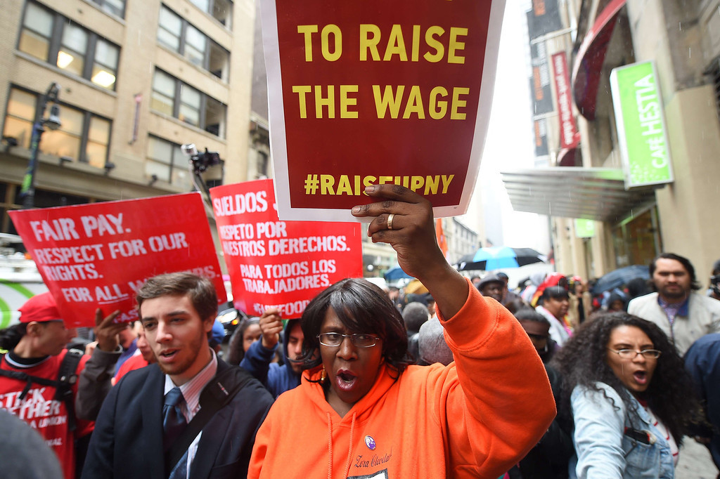 . Fast-food workers hold placards in support to an increase of the fast food workers minimum wage in New York, May 15, 2014. Fast-food workers around the world staged a global protest actions to demand an increase of their minimum wage to 15 USD an hour.    AFP PHOTO/Emmanuel  DUNAND/AFP/Getty Images