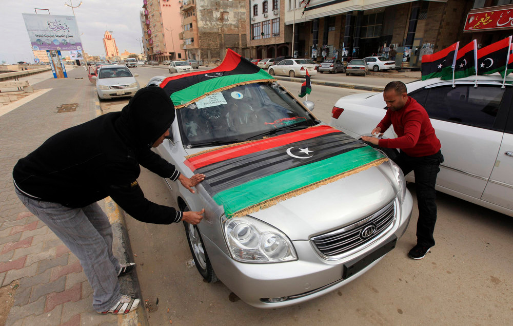 Description of . Men decorate their car with Libyan flags, ahead of the second anniversary of the February 17 uprising, in Benghazi, February 16, 2013. The actual anniversary of the start of the revolt is not until Sunday, but celebrations began on Friday in remembrance of the arrest of a human rights lawyer that kindled the unrest. Cars flying national flags and blasting national songs honked their way through heavy traffic towards the courthouse, where about 2,000 were gathered, chanting anti-government slogans in between celebratory songs and speeches. REUTERS/Esam Al-Fetori