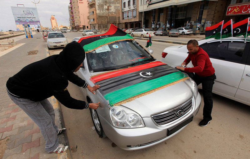 . Men decorate their car with Libyan flags, ahead of the second anniversary of the February 17 uprising, in Benghazi, February 16, 2013. The actual anniversary of the start of the revolt is not until Sunday, but celebrations began on Friday in remembrance of the arrest of a human rights lawyer that kindled the unrest. Cars flying national flags and blasting national songs honked their way through heavy traffic towards the courthouse, where about 2,000 were gathered, chanting anti-government slogans in between celebratory songs and speeches. REUTERS/Esam Al-Fetori