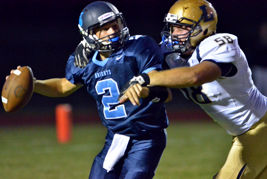 . La Salle defender Keith Wagner ,58, sacks North Penn quarterback Spencer Joner ,2, during first half action of their contest at North Penn High School on Friday August 29,2014. Photo by Mark C Psoras