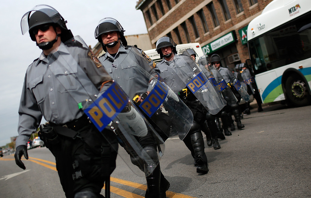 . BALTIMORE, MD - MAY 01: Pennsylvania State Troopers in riot gear deploy near the intersection of North Avenue and Pennsylvania Avenue May 1, 2015 in Baltimore, Maryland. Baltimore authorities are releasing a report on the death of Freddie Gray this morning. Gray, 25, was arrested for possessing a switch blade knife April 12 outside the Gilmor Houses housing project on Baltimore\'s west side. According to his attorney, Gray died a week later in the hospital from a severe spinal cord injury he received while in police custody. (Photo by Win McNamee/Getty Images)