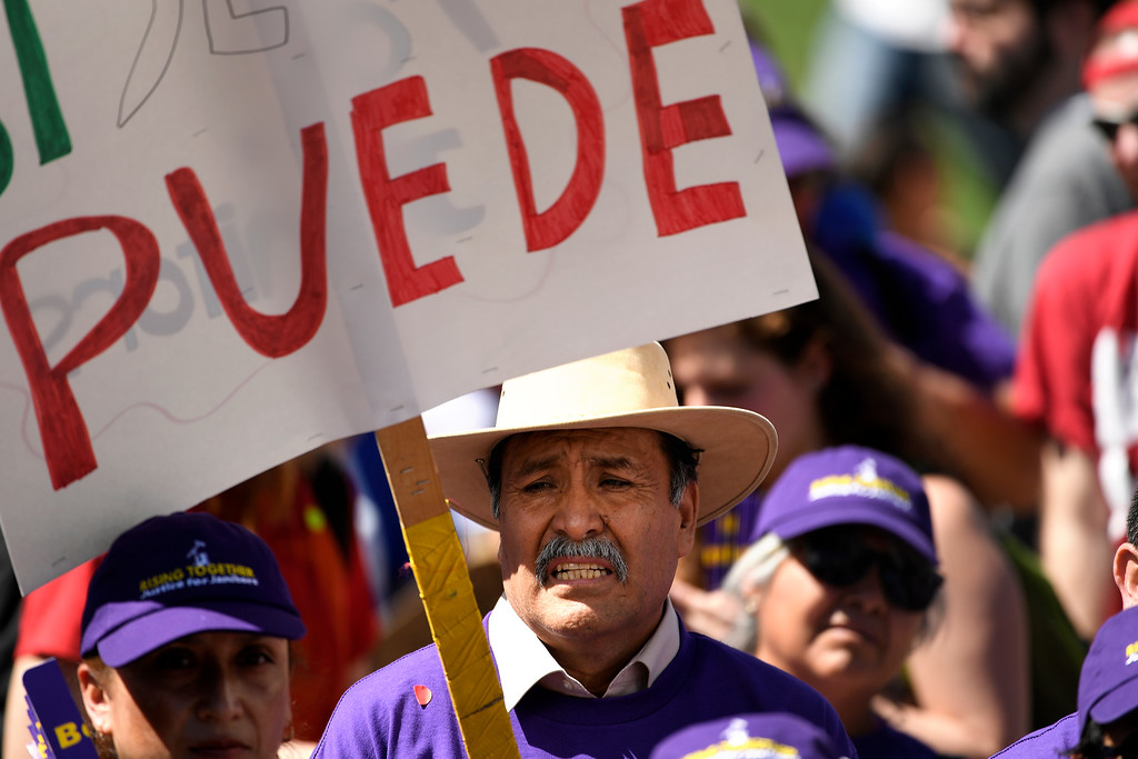 . Denver, CO - ARRIL 14: Jesus Guerrero stands with Denver�s low wage janitors as they kick off their contract campaign with a rally at Civic Center Park�s Veterans Memorial in downtown and a march past all the buildings where they do their work in Denver. The janitors were joined by local homecare workers, Fast food, delivery persons and service workers during their  Underpaid Fight for $15 march. April 14, 2016 in Denver, CO. (Photo By Joe Amon/The Denver Post)