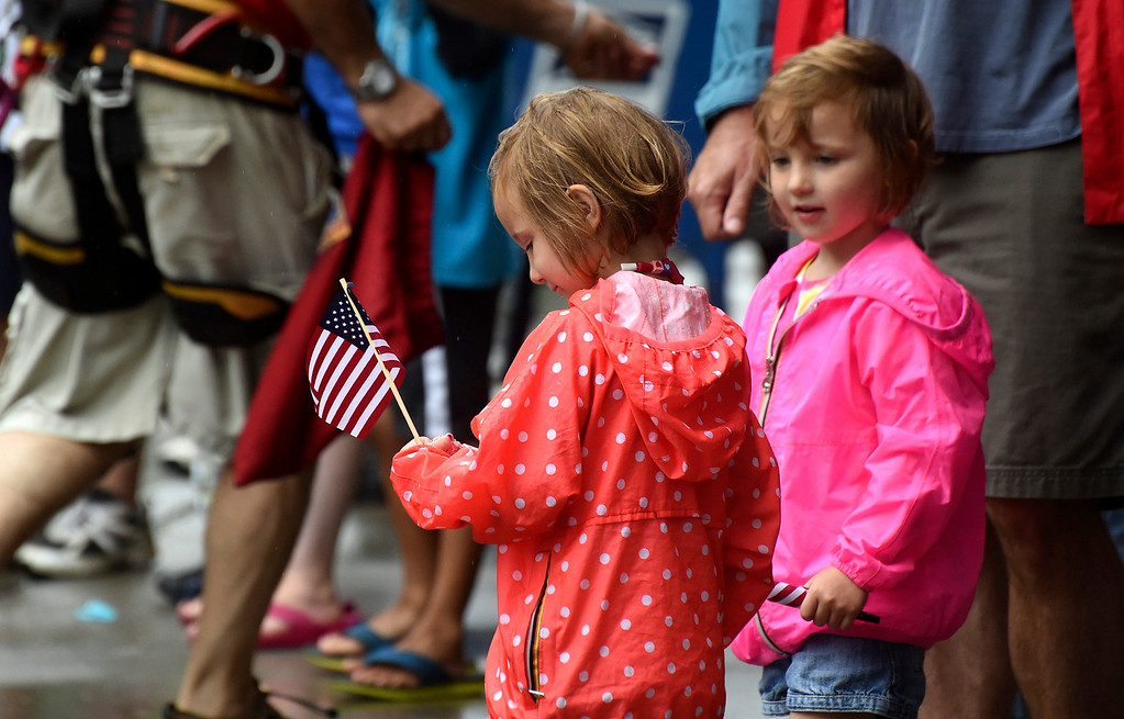 . Kayla Rice/Reformer Alex and Emma Day, 3, of Brattleboro check out their new American flags while watching the Brattleboro Fourth of July parade on Friday.