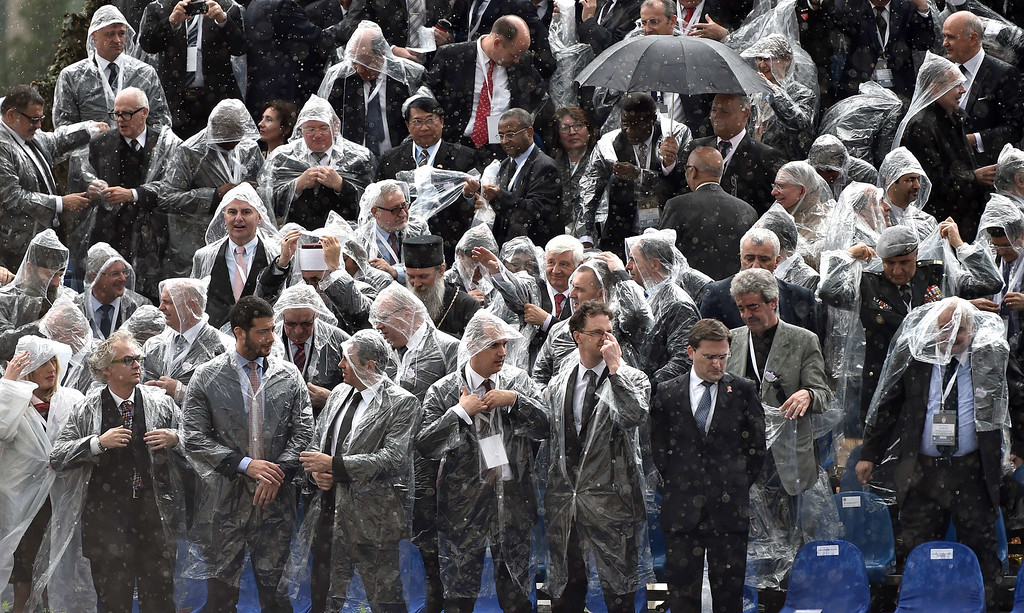 . Serbian government officials and many VIP guests don their plastic jackets during rain showers as they watch a military parade in Belgrade, on October 16, 2014.  ANDREJ ISAKOVIC/AFP/Getty Images