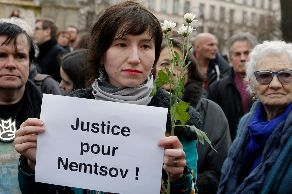 ". A woman holds a paper reading ""Justice for Nemtsov\"" as people gather at Innocent Plaza in central Paris, France, Sunday, March 1, 2015, in memory of Russian opposition leader Boris Nemtsov, and critic of President Vladimir Putin, who was gunned down on Friday, Feb. 27, near the Kremlin in Moscow. Nemtsov was gunned down in Moscow near the Kremlin, just a day before a planned protest against the government. (AP Photo/Francois Mori)"