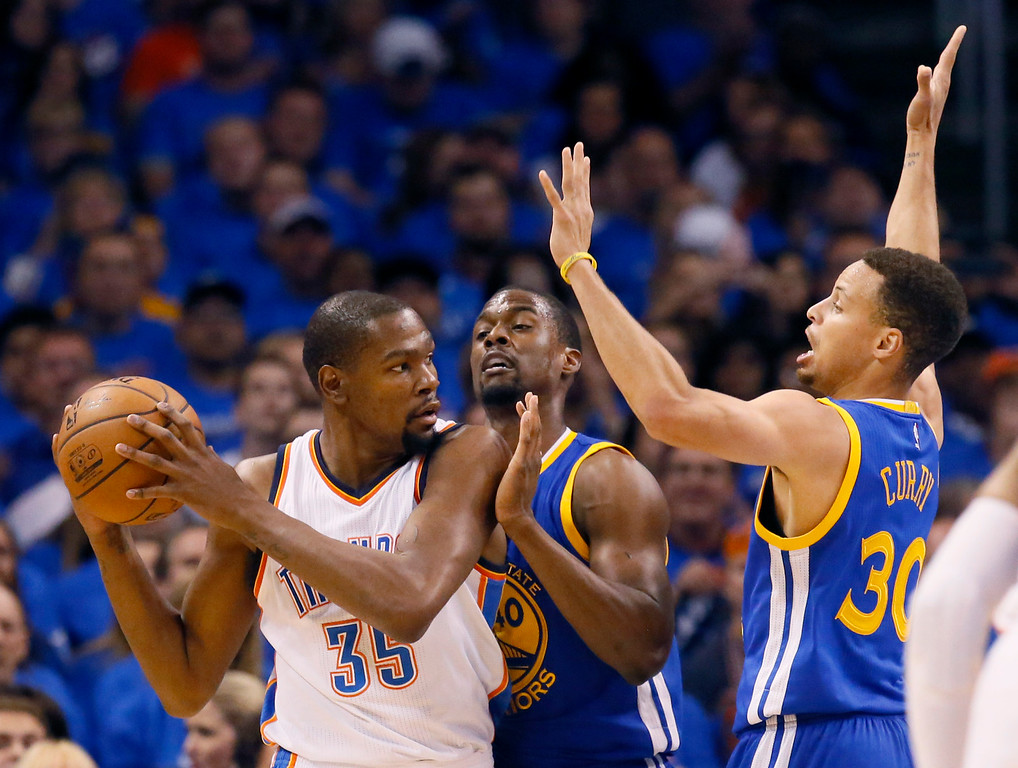 . Oklahoma City Thunder forward Kevin Durant (35) is guarded by Golden State Warriors forward Harrison Barnes (40) and guard Stephen Curry (30) during the first quarter in Game 3 of the NBA basketball Western Conference finals  in Oklahoma City, Sunday, May 22, 2016. (AP Photo/Sue Ogrocki)