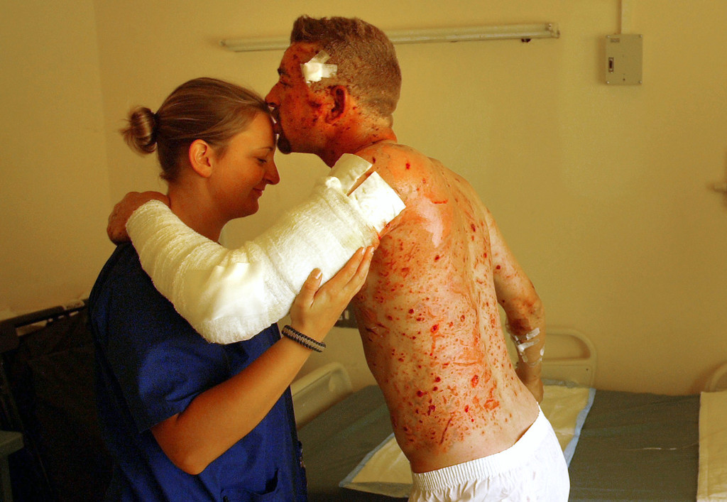 . British private contractor Michael Fitzpatrick thanks his U.S. Army nurse Jayme Sells while recovering from a suicide bomb attack in an American military hospital in Baghdad, Iraq Friday, Oct. 15, 2004. Fitzpatrick said that he was drinking coffee in the Green Zone Cafe when a suicide bomber detonated in one of two explosions that killed 6 people and wounded many more. The U.S. embassy and Iraqi government buildings are located in the heavily fortified area. (AP Photo/John Moore)