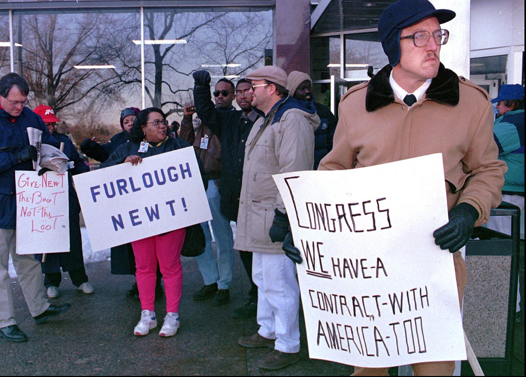 . Dave Glass, of Baltimore, a federal government computer assistant, right, and about 100 other furloughed Social Security Administration workers gather at the Arthur J. Altmeyer Building Tuesday, Dec. 26, 1995 in Woodlawn, Md., to protest the temporary government shutdown. (AP Photo/Gary Sussman)