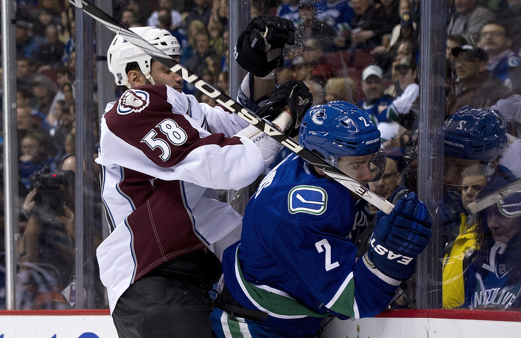 . VANCOUVER, CANADA - JANUARY 30: Dan Hamhuis #2 of the Vancouver Canucks gets taken into the end board by Patrick Bordeleau #58 of the Colorado Avalanche during the first period in NHL action on January 30, 2013 at Rogers Arena in Vancouver, British Columbia, Canada.  (Photo by Rich Lam/Getty Images)