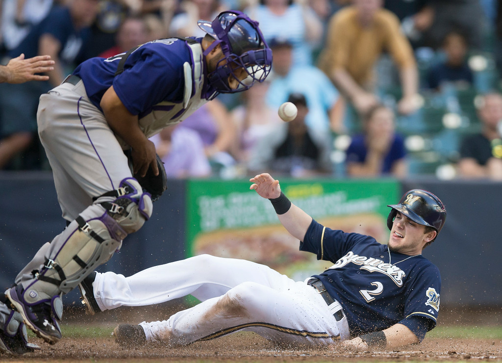 . Scooter Gennett of the Milwaukee Brewers\' slides safely home as Wilin Rosario of the Colorado Rockies\' can\'t make a play on the ball during the fifth inning of a baseball game Saturday, June 28, 2014, in Milwaukee. (AP Photo/Tom Lynn)