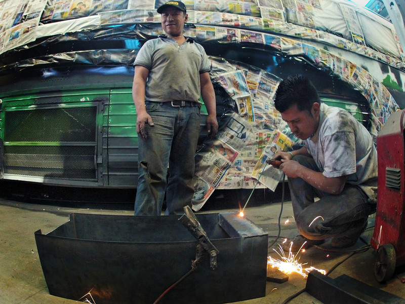 "A welder works on an American school bus in Cuidad Vieja, Guatemala. The bus will be transformed into a ""camioneta"" or ""chicken bus"". Chicken buses are a staple for getting around Guatemala. Chicken bus owners paint their buses in distinctive styles and colors, in part, because so many of their customers are unable to read the stops and locations where each bus will travel. The paint colors and designs help passengers quickly determine which bus to get on. The paint and design scheme reflects the personality of the bus owners as well."