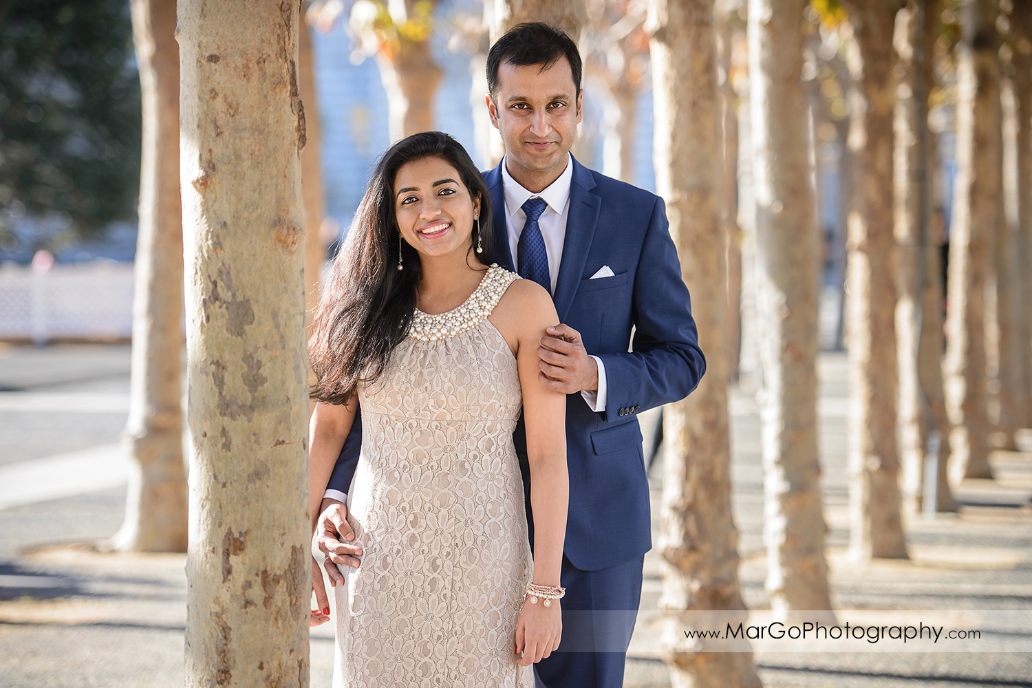 3/4 portrait of woman in beige dress and man in navy blue suit between the trees in front of San Francisco City Hall