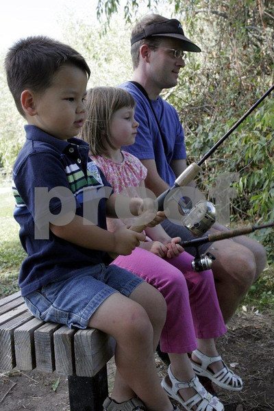 Father teaches two small children the art of patience wile fishing.