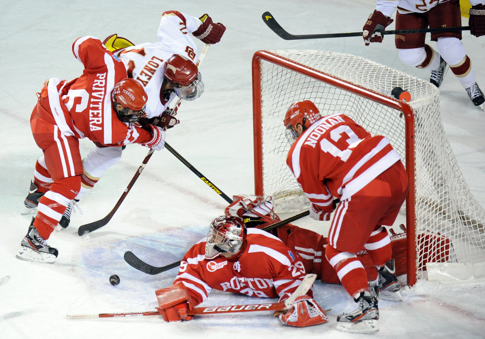 . Boston University goalie Matt O\'Connor (29), Alexx Privitera (6) and Garrett Noonan (13) defend the goal from University of Denver\'s Ty Loney (12) in the 2nd period of the game at Magness Arena in Denver, Colo. on Saturday, December 29, 2012. Hyoung Chang, The Denver Post