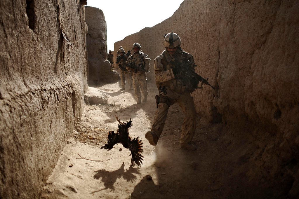 . In this Saturday, Sept. 11, 2010 file photo made by Associated Press photographer Anja Niedringhaus, a Canadian soldier with the 1st RCR Battle Group, The Royal Canadian Regiment, chases a chicken seconds before he and his unit were attacked by grenades shot over the wall during a patrol in Salavat, southwest of Kandahar, Afghanistan. (AP Photo/Anja Niedringhaus, File)