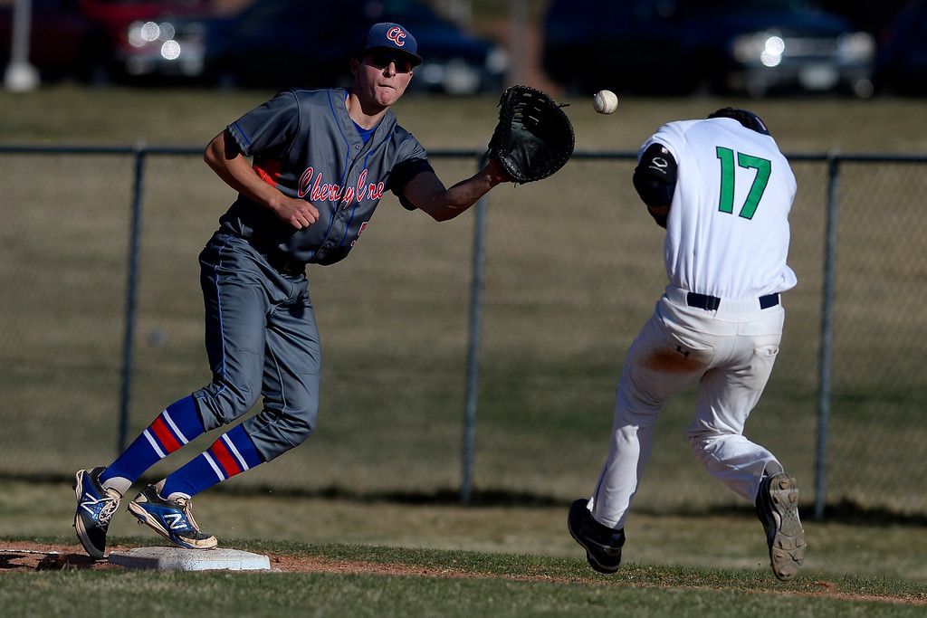 . Aurora, CO - APRIL 08: Jack Gillett (5) of the Cherry Creek Bruins eyes the ball as Jonathan Sanchez (17) of the Overland Trailblazers makes his way to first safely during the fifth inning. Overland hosted Cherry Creek on Tuesday, April 8, 2014. (Photo by AAron Ontiveroz/The Denver Post)