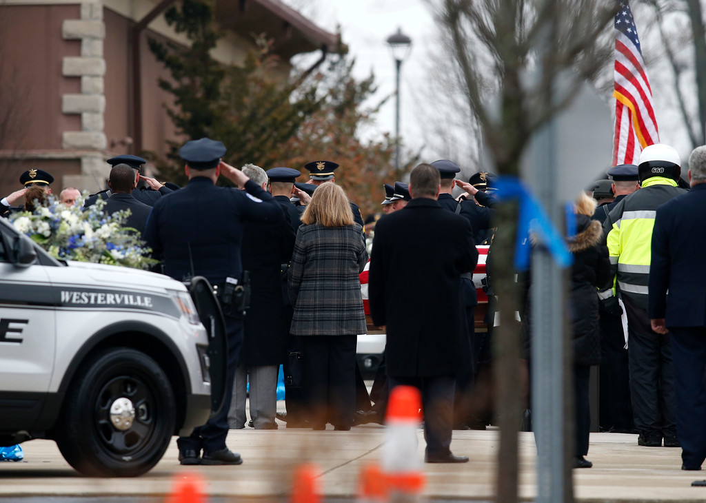 . A casket is taken into St. Paul the Apostle Catholic Church in Westerville, Ohio, before the start of funeral services for Westerville police officers Anthony Morelli and Eric Joering on Friday, Feb. 16, 2018. The two veteran officers were shot after entering a residence on Feb. 10.  (AP Photo/Paul Vernon)
