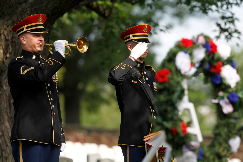 ". An Army honor guard bugler plays ""Taps\"" after a wreath was laid at the gravesite of Army Pvt. William Christman, who was the first military burial at the cemetery, marking the beginning of commemorations of the 150th anniversary of Arlington National Cemetery in Arlington, Va., Tuesday, May 13, 2014.  (AP Photo)"