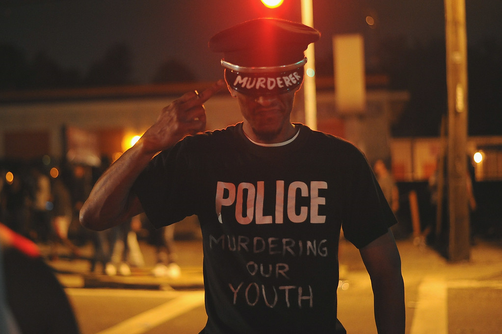 . Protestors demonstrate in Ferguson on August 17, 2014. Riot police hurled tear gas and marched on rioters in Ferguson, the St Louis suburb wracked by race riots since police shot dead an unarmed black teenager on August 9.  AFP PHOTO /Michael B. Thomas/AFP/Getty Images