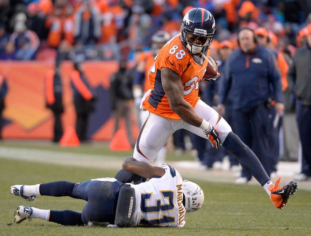 . Denver Broncos wide receiver Demaryius Thomas (88) tries to break a one legged tackle by San Diego Chargers cornerback Richard Marshall (31) during the third quarter. The Denver Broncos vs. The San Diego Chargers in an AFC Divisional Playoff game at Sports Authority Field at Mile High in Denver on January 12, 2014. (Photo by John Leyba/The Denver Post)