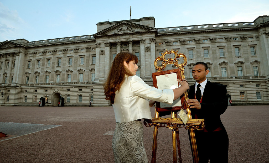 . The Queen\'s Press Secretary Ailsa Anderson with Badar Azim, a footman, places an official document to announce the birth of a baby  boy, at 4.24pm to the William and Kate, the Duke and Duchess of Cambridge at St Mary\'s Hospital,  in the forecourt of Buckingham Palace in London Monday July 22, 2013. The child is now third in line to the British throne.  (AP Photo/John Stillwell, Pool)
