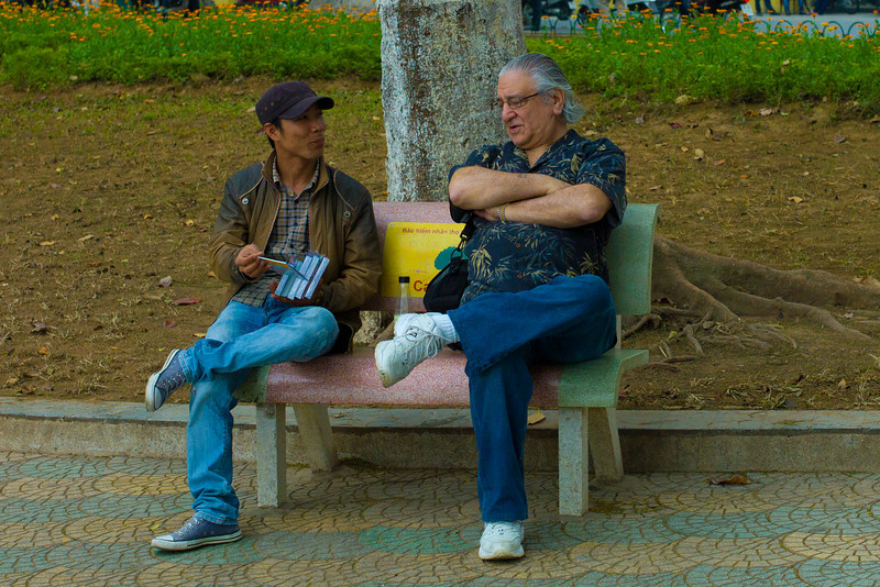 A street salesman gets a lesson in sales from a pro (David Minker) lakeside near the Tortoise Tower in Hoàn Kiếm Lake.