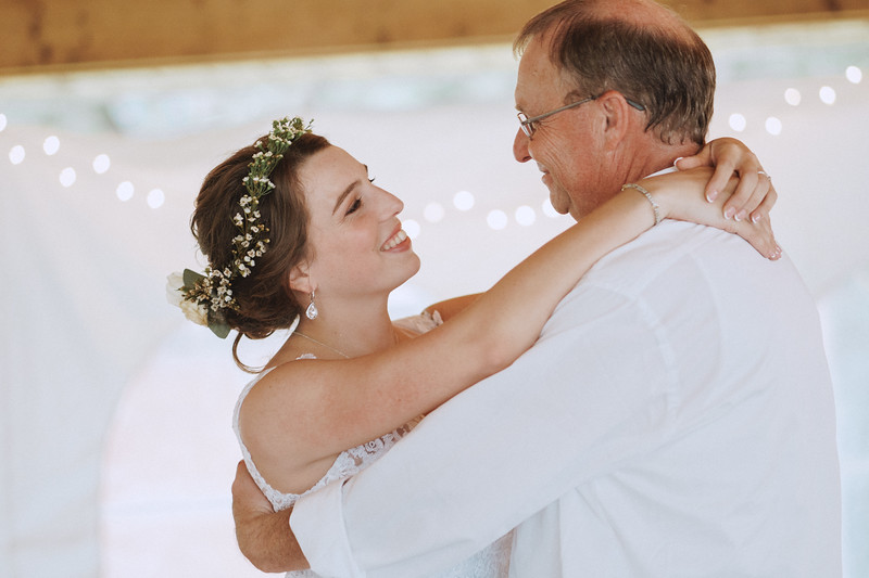 The bride smiles as she dances with her father.