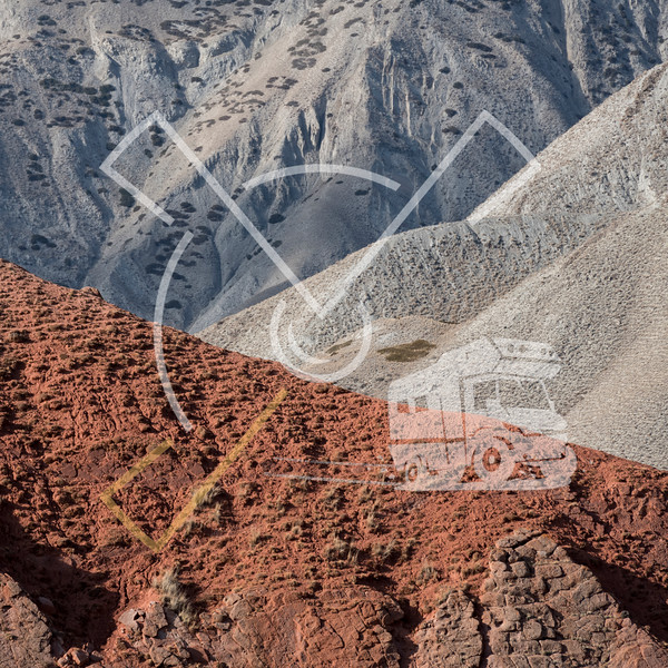 Colorful red hill landscape contrasting against grey hills in the Arpa valley along the Arpa and Jamanti river in the Tian Shan mountains