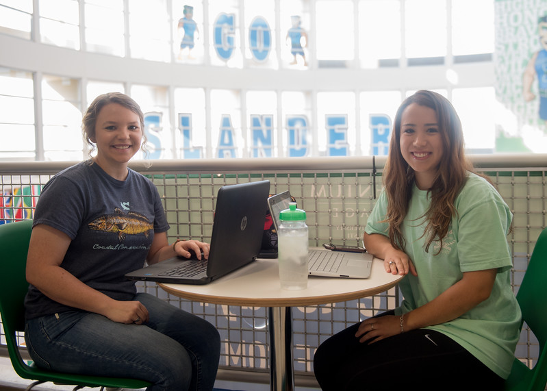 Students Emalee Keim (left) and Mayra Rodriguez take a break from studying in the University Center for a photo.