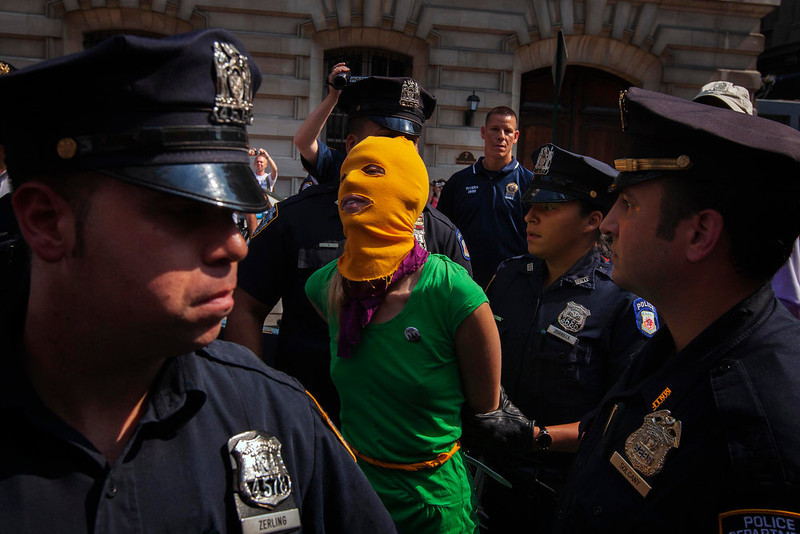 ". New York Police Department officers arrest a woman demonstrating in solidarity with the Russian punk band Pussy Riot in front of the Russian Consulate in New York August 17, 2012. Three women from Russian punk band Pussy Riot were sentenced to two years in jail on Friday for their protest against President Vladimir Putin in a church, an outcome supporters described as the Kremlin leader\'s ""personal revenge.\""   \""Pussy Riots\"" ranked as Google\'s tenth most searched trending event of 2012. REUTERS/Lucas Jackson"