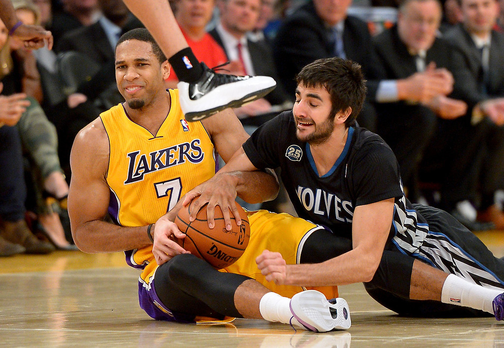 . The Lakers\' Xavier Henry and Timberwolves\' Ricky Rubio hit the hardwood for a loose ball in the first half, Friday, December 20, 2013, at Staples Center. (Photo by Michael Owen Baker/L.A. Daily News)