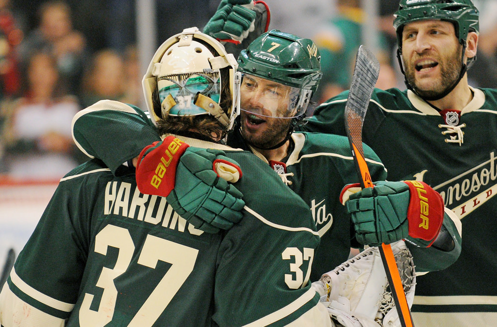 . Minnesota\'s Matt Cullen, center and Mike Rupp, right, congratulate goalie Josh Harding, who stopped 25 of 27 shots in their 3-2 overtime win against Chicago. (Pioneer Press: John Autey)