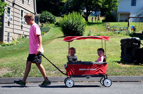 7/10/2018 Mike Orazzi | Staff Matthew Elwell gives a covered wagon ride to Parker Elwell and Abigail Grimes on Lake Plymouth Blvd. in Plymouth Tuesday afternoon.