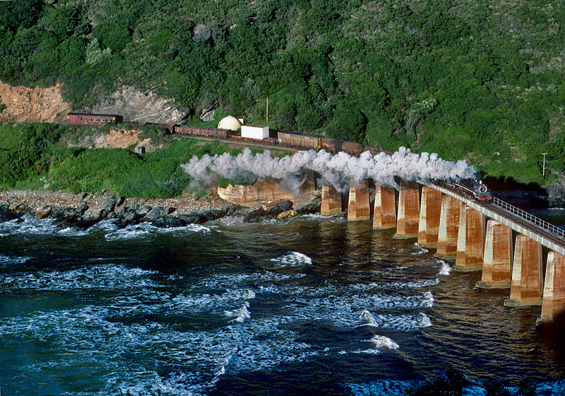 A mixed train to Knysna crosses the Kaaimans River bridge. This was one of the classic photo locations back in the old days. As South African Railways rationalized their network and closed branch lines, the Knysna branch survived as a steam powered tourist line. But more recently the line was closed by a landslide and has never been reopened.  October 1983.