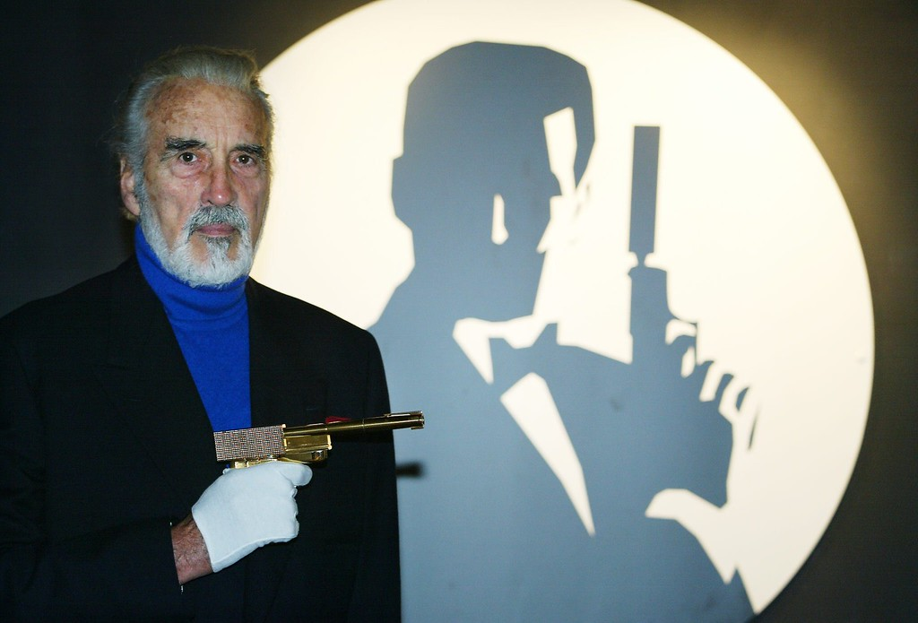 ". This photo taken on October 15, 2002 shows actor Christopher Lee holding the golden gun beside the Bond logo during the opening of the \'Bond, James Bond\' exhibit at The Science Museum in London. The golden gun used by villain Scaramanga in the James Bond movie ""The Man With The Golden Gun\"" has been stolen from its film studio home, British police said on October 11, 2008, according to the BBC. The prop, one of the most iconic weapons in cinema history, was noticed missing from Elstree Studios, north of London, on October 10, 2008, Hertfordshire Constabulary said.        (ADRIAN DENNIS/AFP/Getty Images)"