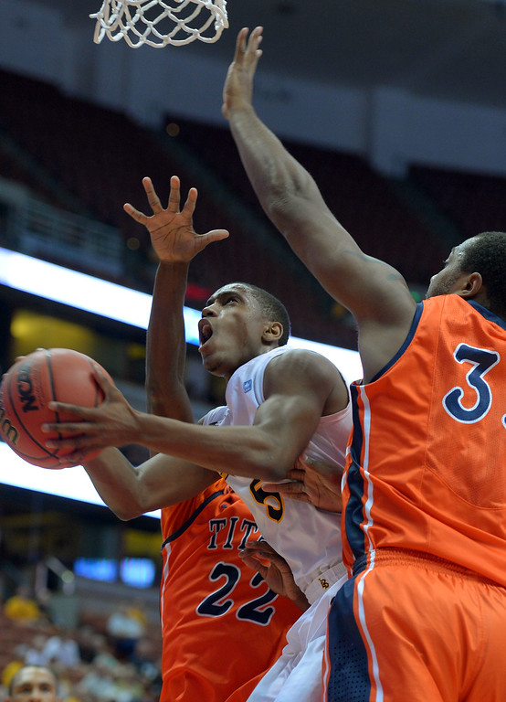 . Under the basket, LBSU\'s Mike Caffey is fouled by CSUF\'s James Johnson, right, at the Honda Center in Anaheim, CA on Thursday, March 13, 2014. Long Beach State vs CSU Fullerton in the Big West men\'s basketball tournament. 1st half. LBSU won 66-56.  Photo by Scott Varley, Daily Breeze)