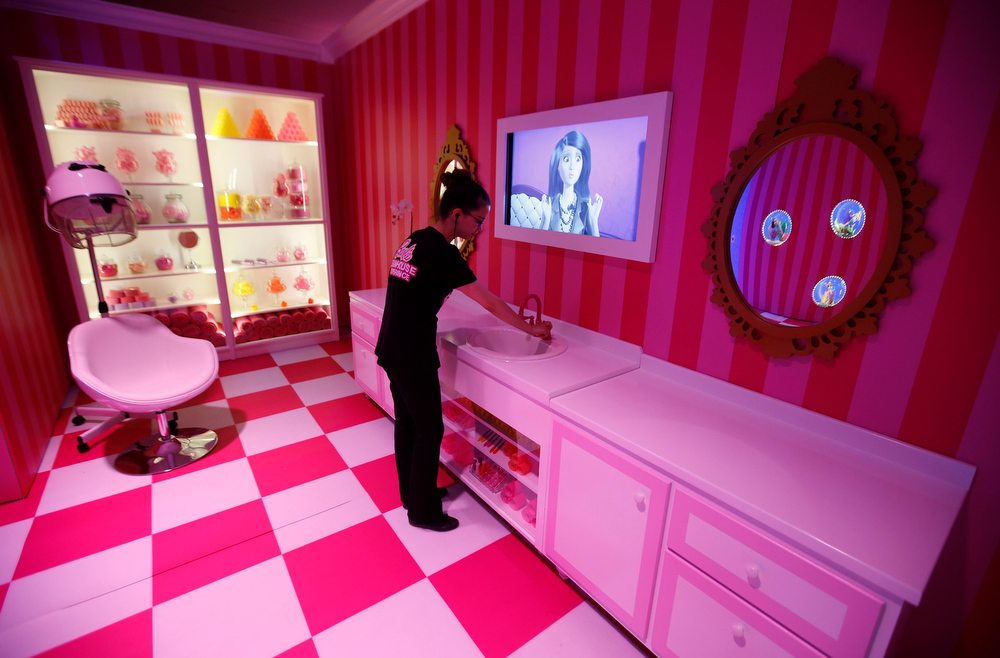 """. A staff poses for the photographer inside a life-size \""""Barbie Dreamhouse\"""" of Mattel\'s barbie dolls in the bathroom during a media tour in Berlin, May 15, 2013. The life-sized house, covering about 1,400 square metres offers visitors to try on Barbie\'s clothes in her walk-in closet, tour her living room and her kitchen.   REUTERS/Fabrizio Bensch"""