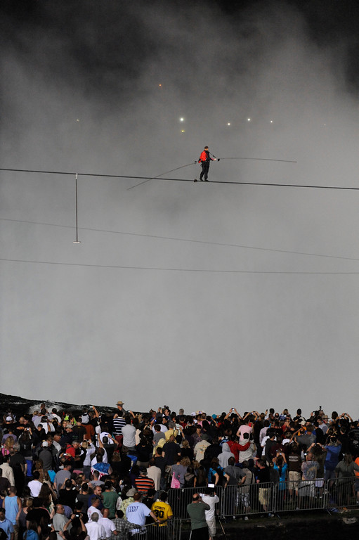 . Nik Wallenda walks across Niagara Falls on a tightrope as seen from Niagara Falls, N.Y., Friday, June 15, 2012. Wallenda has finished his attempt to become the first person to walk on a tightrope 1,800 feet across the mist-fogged brink of roaring Niagara Falls. The seventh-generation member of the famed Flying Wallendas had long dreamed of pulling off the stunt, never before attempted.  (AP Photo/Gary Wiepert)
