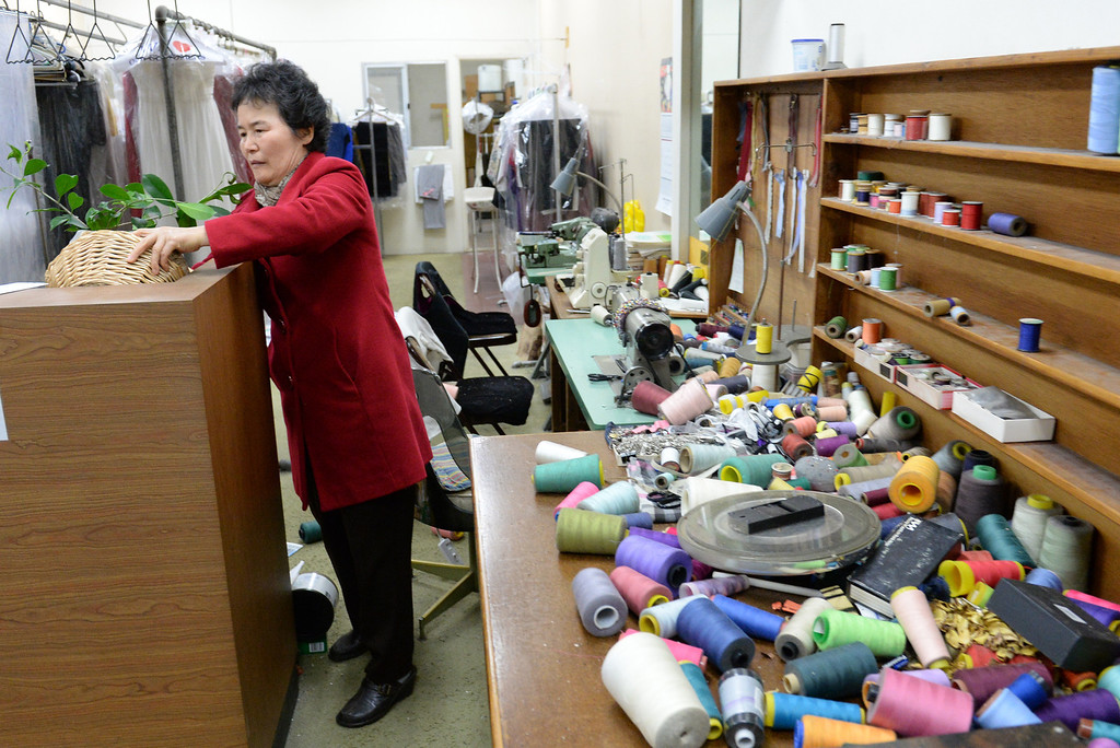 . Sherry Kim, owner of Towne Cleaners, looks over the damage after the 5.1 eartchquake at her shop in La Habra on Friday March 28, 2014. (Staff Photo by Keith Durflinger/Whittier Daily News)