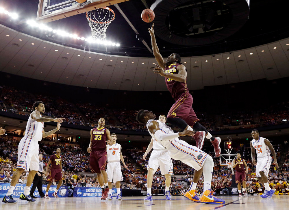 . Minnesota\'s Trevor Mbakwe (32) charges into Florida\'s Will Yeguete during the first half of a third-round game of the NCAA college basketball tournament, Sunday, March 24, 2013, in Austin, Texas. (AP Photo/David J. Phillip)