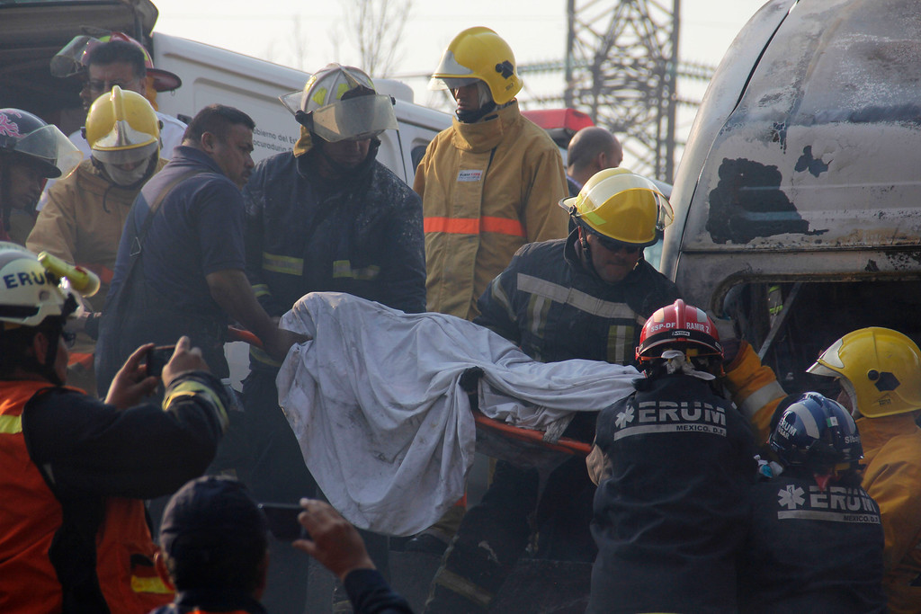 . Firefighters remove a body from a destroyed home after a gas tanker truck exploded on a nearby highway in the Mexico City suburb of Ecatepec early Tuesday, May 7, 2013. The blast killed and injured dozens, according to the Citizen Safety Department of Mexico State. Officials did not rule out the possibility the death toll could rise as emergency workers continued sifting through the charred remains of vehicles and homes built near the highway on the northern edge of the metropolis. (AP Photo/Gabriela Sanchez)