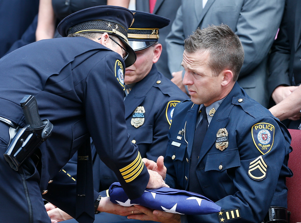 . Oklahoma City police officer Sgt. Ryan Stark, right, accepts the flag from the casket of his canine partner, K-9 Kye, following funeral services for the dog in Oklahoma City, Thursday, Aug. 28, 2014.  (AP Photo/Sue Ogrocki)