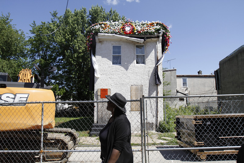. People arrive for an event at the site of an abandoned home in the impoverished Mantua section of Philadelphia on Saturday, May 31, 2014. The cultural and memorial project called �Funeral for a Home� celebrated the dilapidated row house\'s colorful life before it was knocked down. (AP Photo/Jessica Kourkounis)