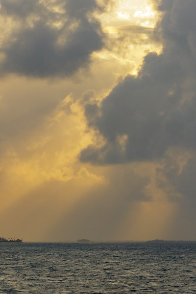 Orange sunset with storm clouds and tropical islands of the Caribbean Sea