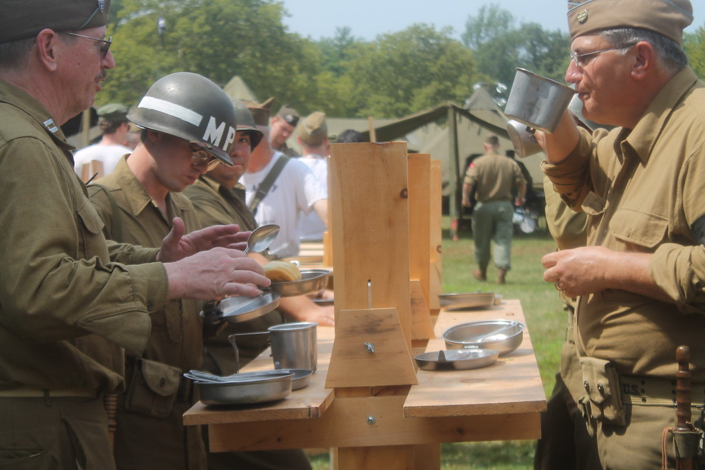 . Reenactors representing the USA Army eat in the same manner the Army would have eaten if in they were in a secure area during the D-Day Conneaut event.  Meals like this would any happen in a secured area because soldiers lined up anywhere make an easy target. Kristi Garabrandt - The News-Herald