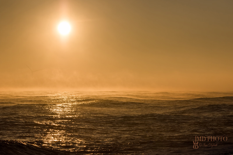 Seascape sunrise. Beautiful misty morning sun over sea with background wind turbine.