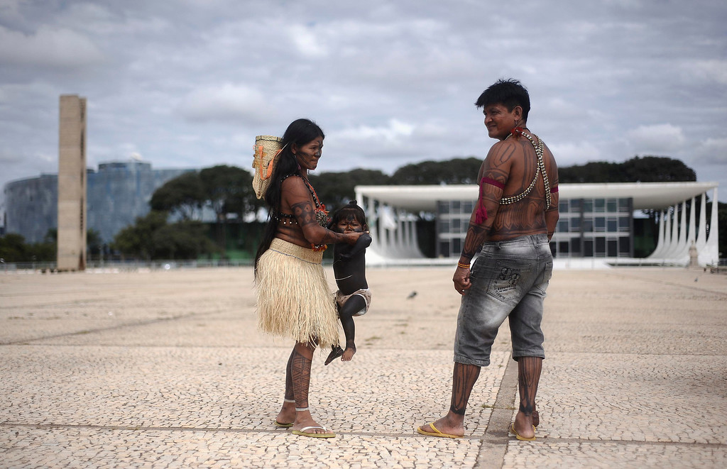 . A Munduruku Indian family walks at the esplanade in front of Planalto Palace during a protest, where they were prevented by security forces from entering the palace, in Brasilia June 6, 2013. The Indians from the Amazon Basin are demonstrating against violations of indigenous rights and calling for the suspension of the construction of the Belo Monte hydroelectric plant on the Xingu river, a huge project aimed at feeding Brazil\'s fast-growing demand for electricity. REUTERS/Lunae Parracho